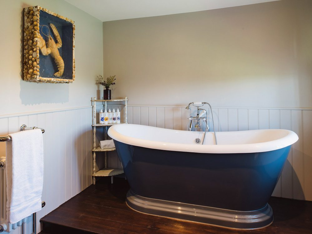 Blue roll top bath at Kingshill farmhouse on the Elmley Nature Reserve. Interior design & styling by Rowan Plowden Design.