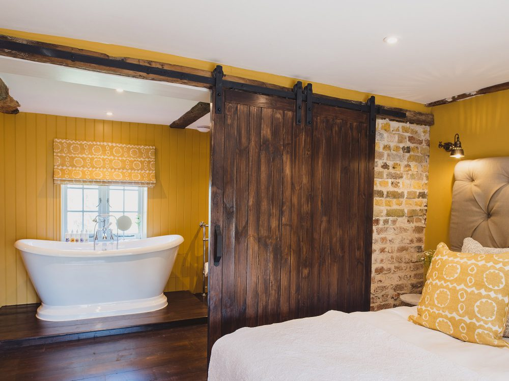 The yellow bedroom with en-suite at Kingshill farmhouse on the Elmley Nature Reserve. Interior design & styling by Rowan Plowden Design.