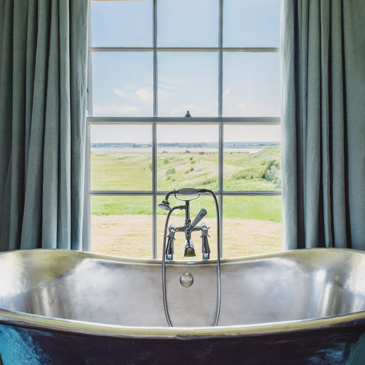 Pewter roll top bath at Kingshill farmhouse on the Elmley Nature Reserve. Interior design & styling by Rowan Plowden Design.